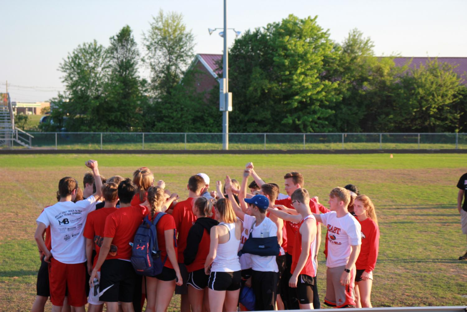 The team getting together before a meet in a huddle.
