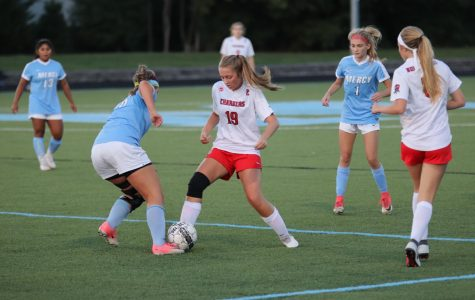 Junior Chloe Holt fighting for possession of the ball in the girls soccer game against Mercy. The Chargers have beat Mercy twice this year, and are looking for another win this upcoming Friday.