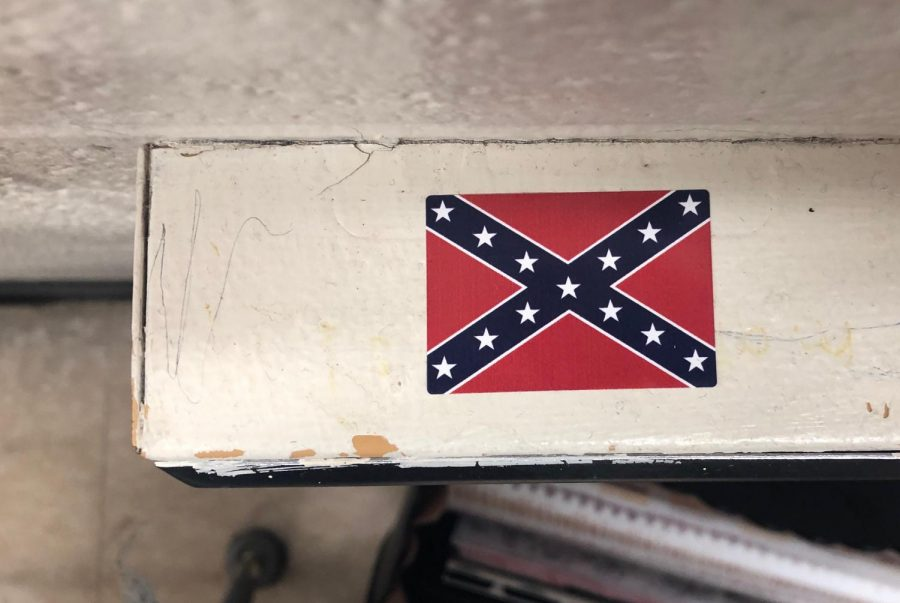 This is a Confederate flag sticker on the top of an outlet in a classroom in second hall. The stickers have also been found in other classrooms in different locations.