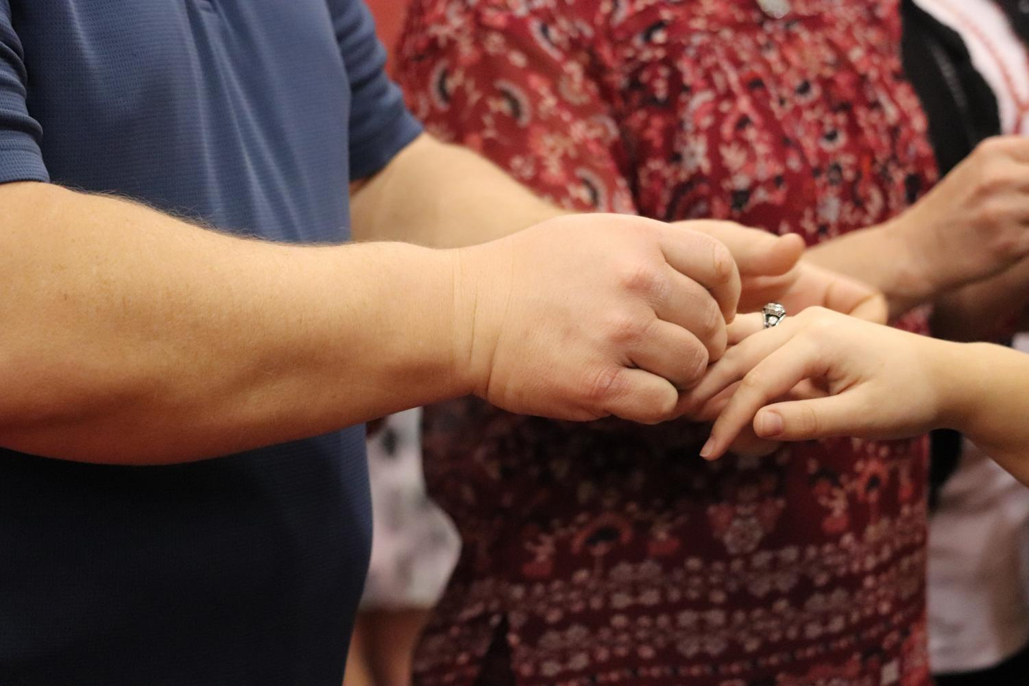 Father presents daughter's ring in the junior ring ceremony.