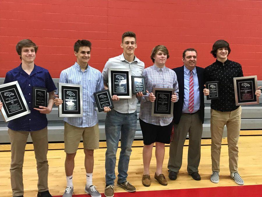 The+boys+basketball+teams+five+seniors+from+last+season%2C+holding+their+awards++with+head+coach%2C+Jason+Couch
