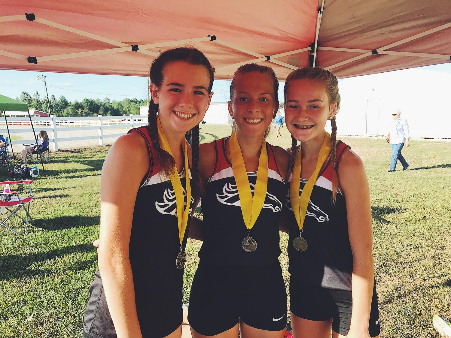 Sophomore Mia Maguire (left), junior Emily Tinelli (middle) and freshman Raelee Hawkins (right) all excelled in their meet Sept. 14. All three girls placed in the top 10 out of 69. Coach Lenny Raley calls them the