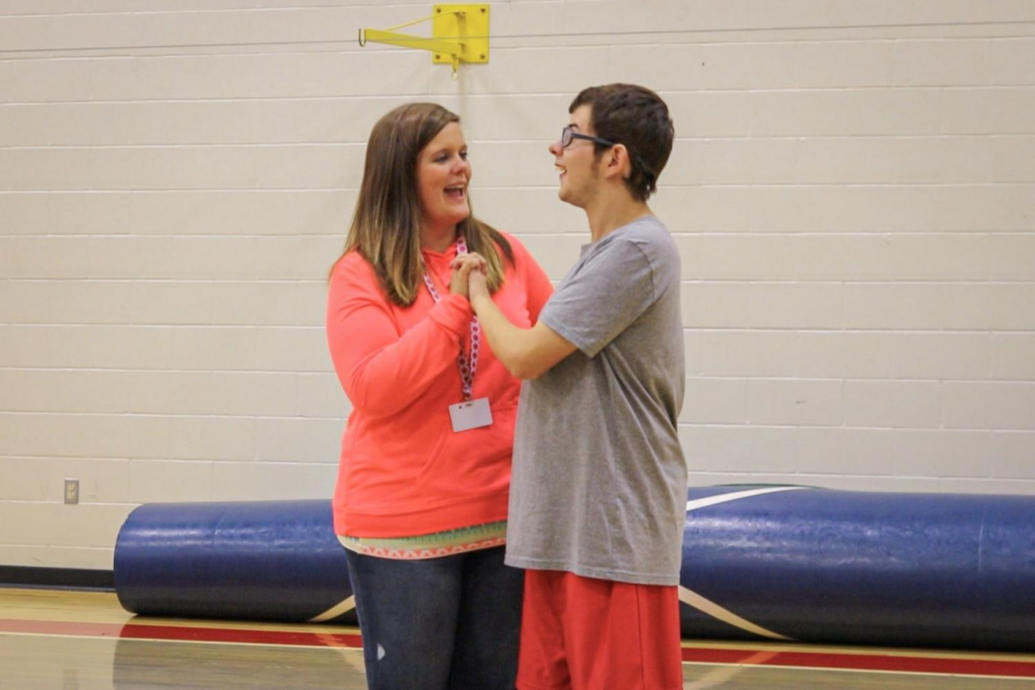 Celebrating junior Braden High's homerun, Instructional Assistant Katie Hoben is congratulating High on his hard work and dedication while playing baseball. Bullitt East offers two adaptive classes, P.E. and music alive, which contains  special needs students along with peer partners.