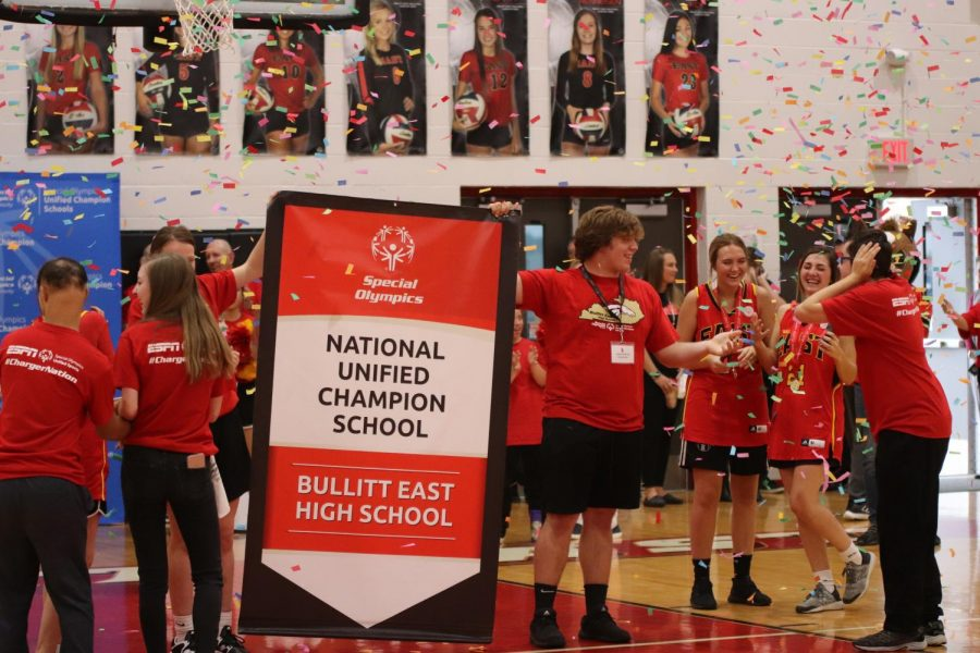 Senior+Conner+Groves+holds+the+National+Unified+Champion+School+banner+in+front+of+the+crowd.+ESPN+and+Special+Olympics+presented+this+banner+during+the+assembly.+Groves+said%2C+%22It+was+very+cool+seeing+the+kids+in+the+club+so+excited+and+for+the+whole+day+to+just+be+about+them.