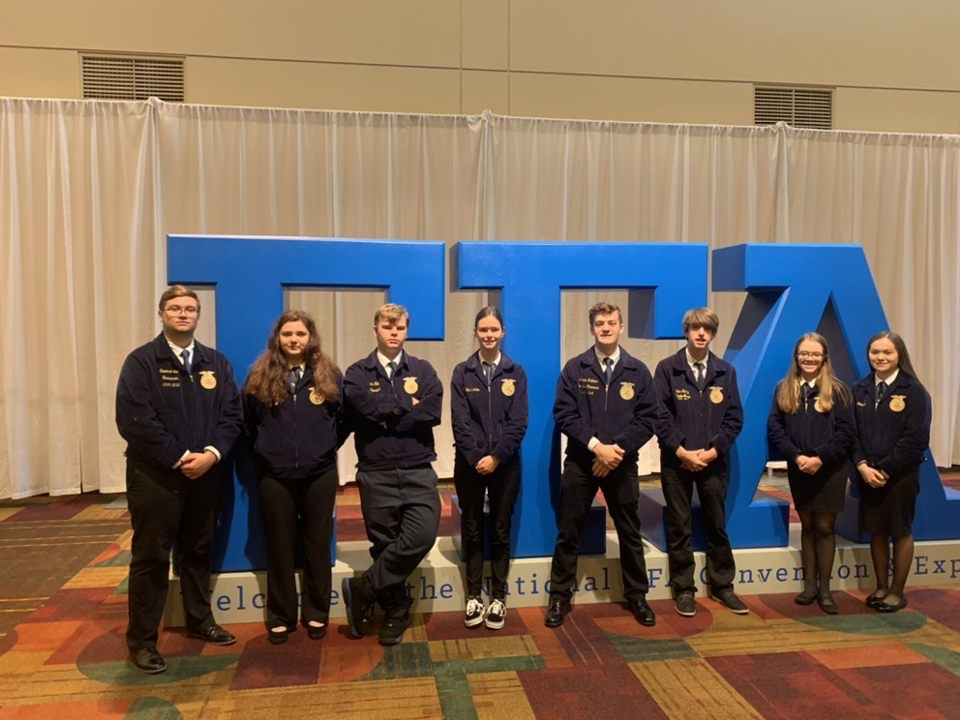 """The members from the Bullitt East and North Bullitt FFA chapters who attended the trip line up next to the FFA sign in the entrance of the convention. They were able to meet fellow FFA members and attend workshops to grow their leadership skills. """"The workshops that I attended while on the convention showed me how to stop outside of my box and talk to new people while also becoming a leader when needed,"""" said junior Madi Wilhite."""