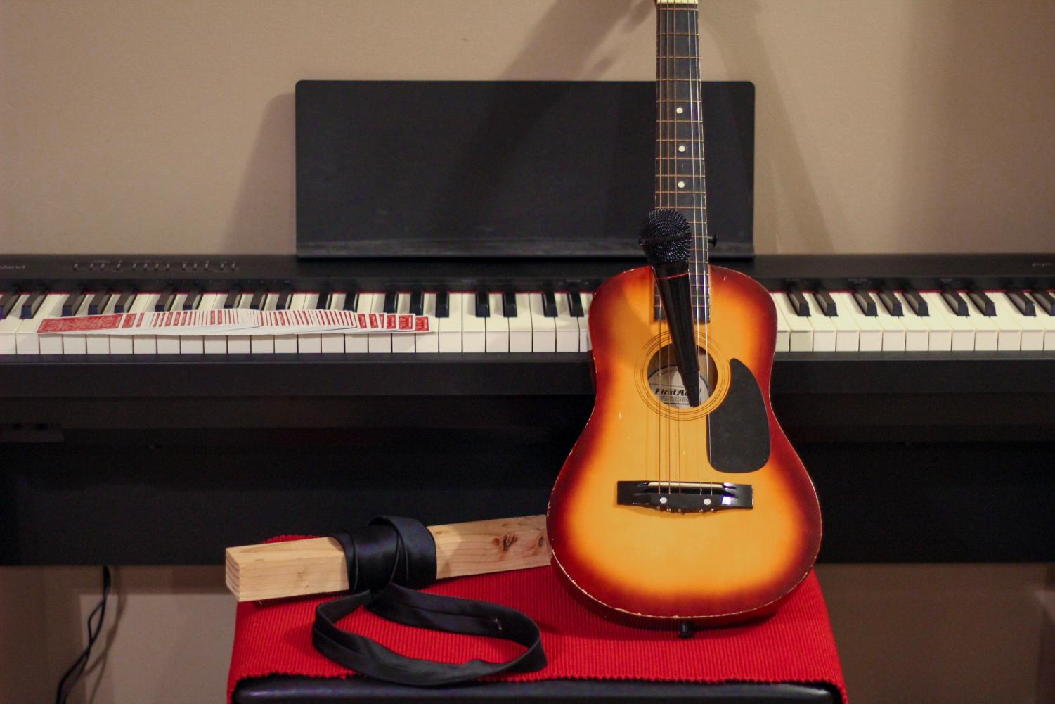 """A guitar and piano to represent the instruments that are going to be played, a block of wood with a karate belt wrapped around it to represent the karate act, the """"Red Monarchs"""" by Theory Eleven deck of cards to represent the magic act, the red carpet to represent the dance act and how they perform on a platform and a microphone to represent the singers. """"I think it's going to be a good talent show, because there's a variety of talents that are going on, and I just think it'll be good this year,"""" said sophomore Trinity Smith."""