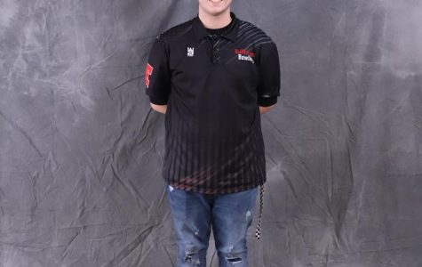 """Junior Adam Young posing in front of a screen for a photo. Young is the fourth best bowler on the bowling team, with an average of 181. """"I feel like it's going to progress really well. We're doing pretty good right now, staying consistent. I hope that we can make it to at least regionals, and win; go to state overall,"""" said Young."""
