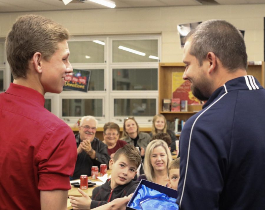 "Senior Aiden Robison handing the ""Region 5 Coach of the Year"" award to Coach Kyle Downs. During Robison's speech, he pulled out a gift bag, with an award for Downs being named the ""Coach of the Year,"" from their regionals match. ""I didn't do anything different this year than I did in any other past years. You know, you win awards, and you don't win awards, and it's always nice to win it, but it's not something that I look forth, at the beginning of the year,"" said Downs, ""It's cool to get it, I've gotten it twice. You know, I'm two time defending FBLA Region Adviser of the Year, and you know, they're cool to get; to get awards and stuff like that, it means that you're kind of doing a good job, but it also means that you have good people around you, you have good players, you have good support, and at the end of the day, it's an award, and it's nice to have, but, you know it's not about me, it's about the kids, and as long as they're being successful, then I'll be fine whether I get one of those, or not."""