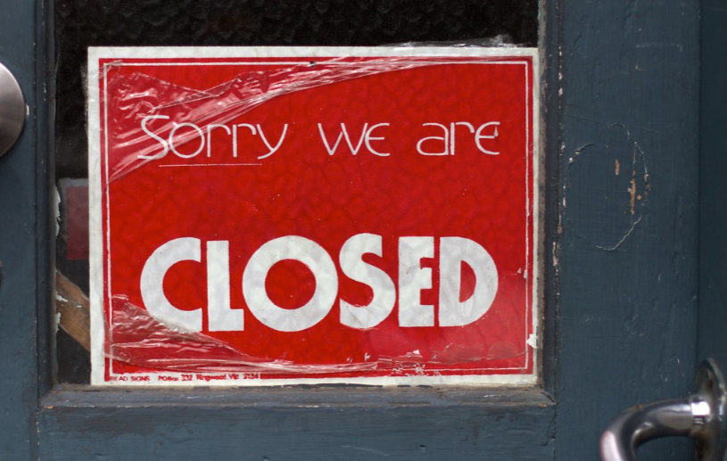 A closed sign being put on display in the window of a business.