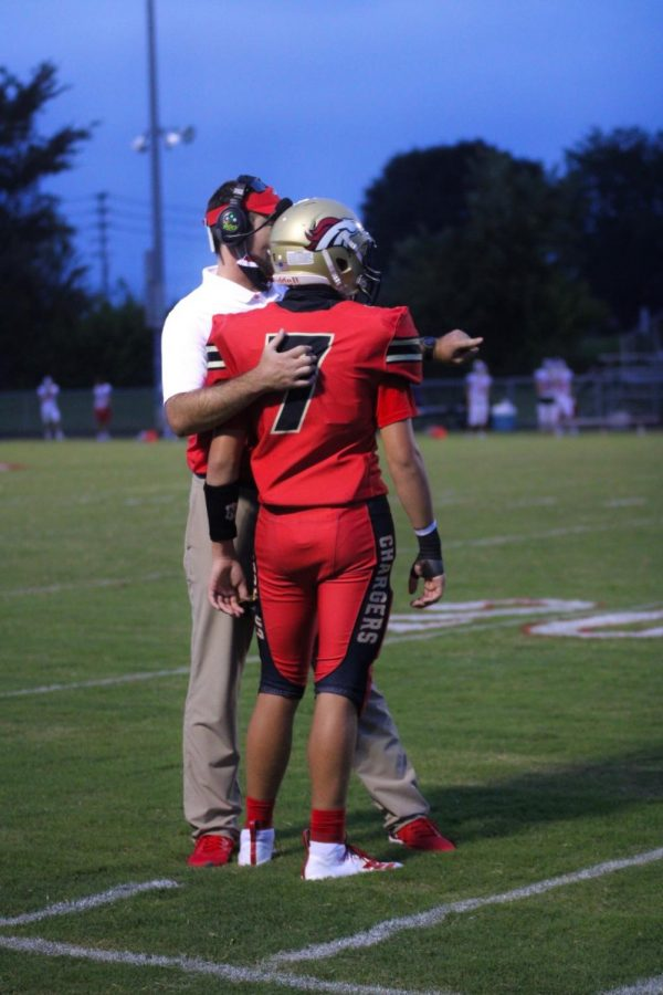 "Head Football Coach Ethan Atchley talking to freshman Jack Zwernemann about a plan, at the Sept. 11 Christain Academy versus Bullitt East football game.  ""I think our players have done a great job of accepting constant change, and adapting. They've been willing to go through a whole lot of different procedures that we have been asked to place. We have a lot of different things to try and keep our kids, and community, safe, but still give the kids an opportunity to play football,"" said Receivers Coach Tyler Faucett."