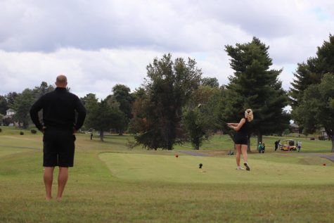 Coach Larry Steinmetz watches as sophomore Macie Brown tees off. Brown