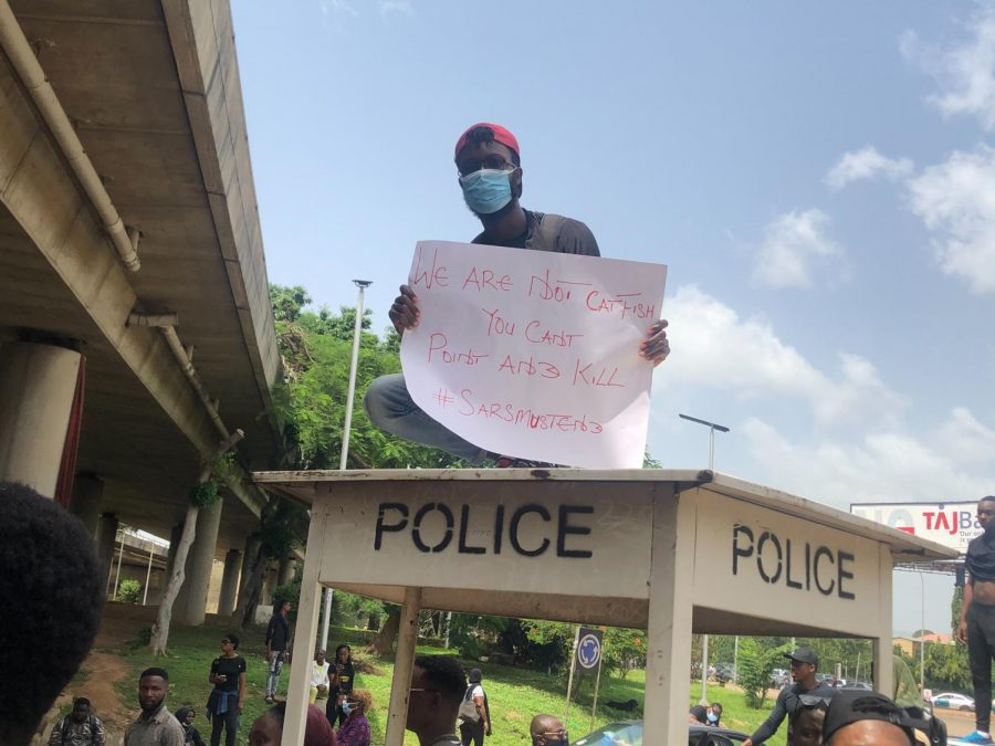 Nigerian man peacefully protesting holding sign stating,