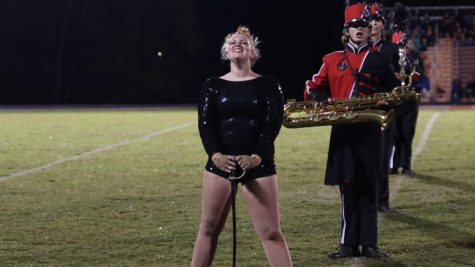 Color guard member stands tall with enthusiasm finishing a great performance at the Grayson County High School marching band competition.