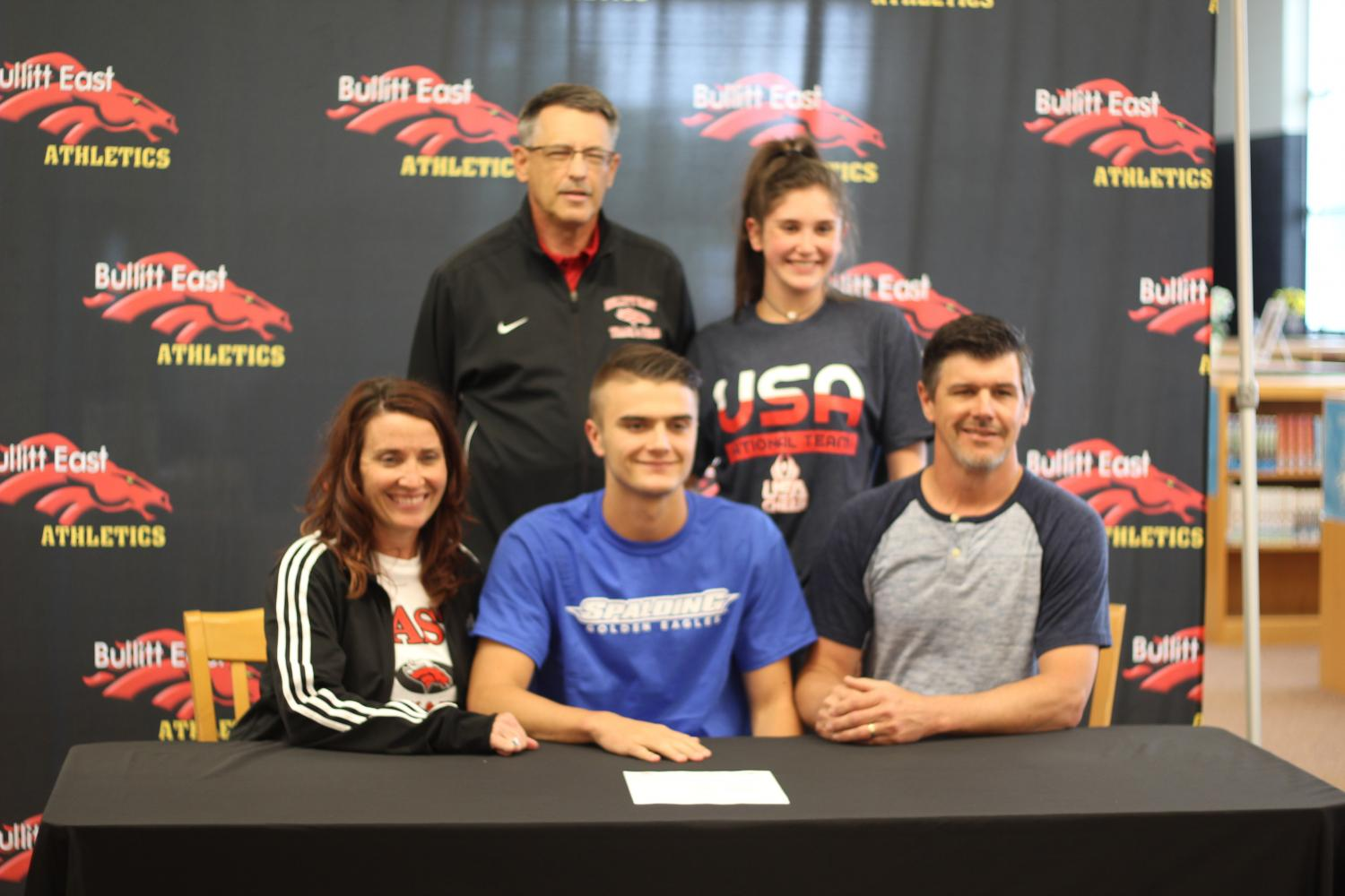 On+May+1%2C+Senior+Connor+Green+signs+with+Spalding+University+to+run+track.+Along+with+him+is+his+family+and+his+track+and+field+coach%2C+Lenny+Raley.