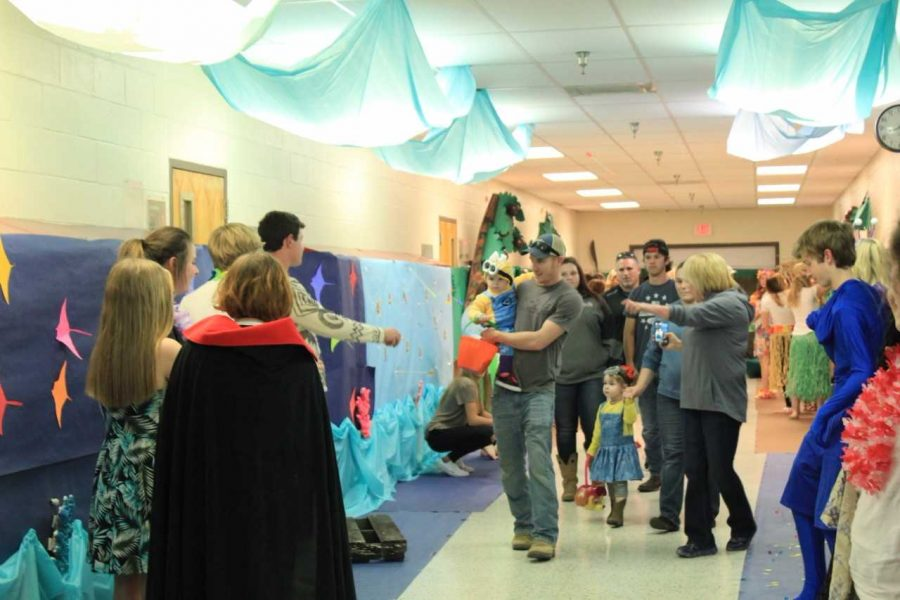 Parents and children walk down the halls while attending Halloween in the Halls.