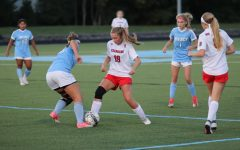 "Junior Chloe Holt fighting for possession of the ball in the girls soccer game against Mercy. The Chargers have beat Mercy twice this year, and are looking for another win this upcoming Friday. ""Chloe is a great player and exerts confidence when she carries the ball,"" said Mahoney."