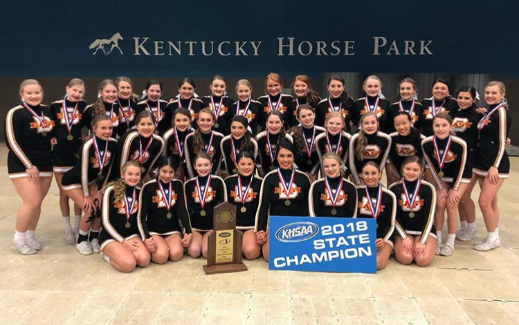 The cheerleading team is posing with the state championship trophy. They have won the KHSAA cheerleading state championship title the past five years.
