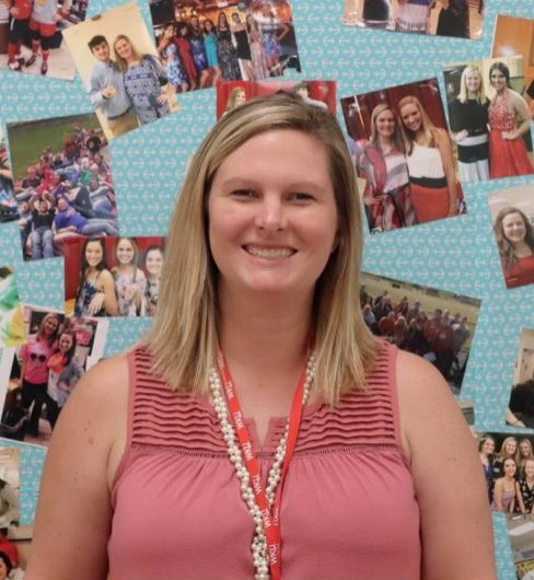 Walker standing in front of a board full of pictures with former students. Through the years Walker has taught, whenever a student took a picture with her, she placed it on the board.
