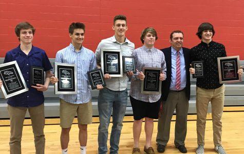 The boys basketball teams five seniors from last season, holding their awards  with head coach, Jason Couch