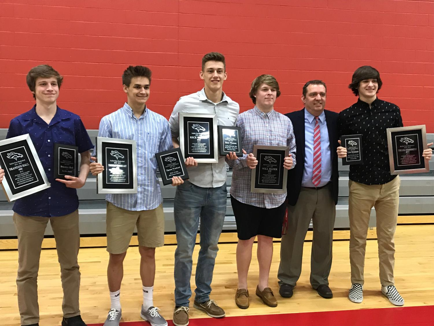 The boys basketball teams five seniors from last season, holding their awards  with head coach, Jason Couch