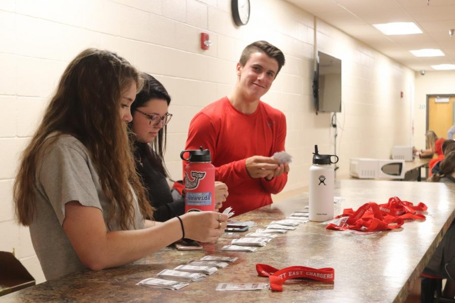 Junior Aeron Adams handing out PBIS barcodes and lanyards with fellow SLAM class peers at lunch. With the new rewards system each student has to have their own code for teachers to scan and give them points.