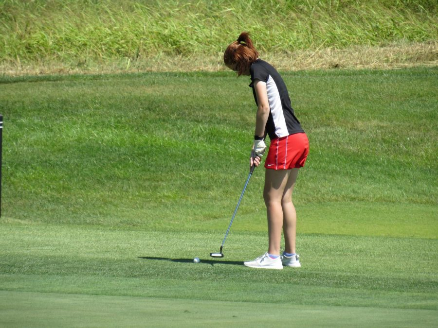 Putting the golf ball, senior Abi Huffman about to make her final shot into the hole. On Aug. 24 the girls golf team competed in a tournament at their home course, Heritage Hill.