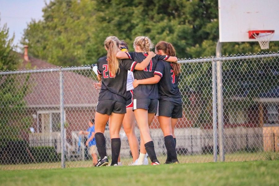 Seniors Rylee Ortaga and Emily Ezell help junior Bailey Chitwood off the field after being tackled by Male goalie.