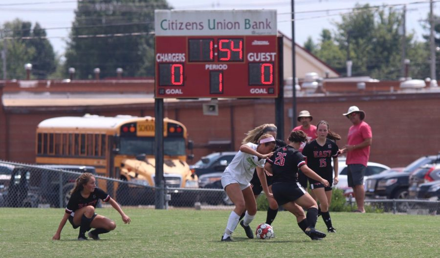 Fighting for possession, seniors Brooke Montague and Ryley Ortega try to keep Owensboro Catholic from scoring. This was their first home game of the season and resulted in a tie.