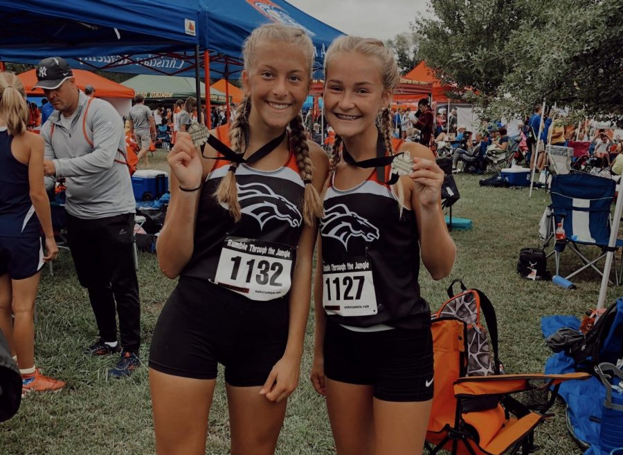 Freshman Raelee Hawkins and junior Emily Tinelli show off their placement medals. They placed high in last weekend's Hillbilly Run.