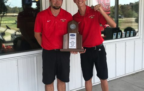 "Coach Kyle Downs and senior Aiden Robison holding trophy of second place from regionals. The boys golf team placed second at regionals on Oct. 1, against 12 other teams, and Robison and junior Thomas Bryan earned a spot in the state tournament. ""Thomas and I are going to get prepared for state by playing a ton. We want to show the state that Bullitt East has some great golfers,"" said Robison."