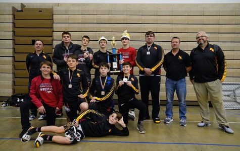 The wrestling team poses with their trophy. The team had seven top four placers in their tournament. They look to build onto this success as the season goes on.