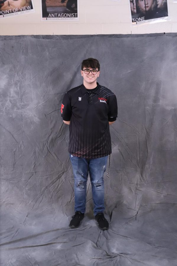 "Junior Adam Young posing in front of a screen for a photo. Young is the fourth best bowler on the bowling team, with an average of 181. ""I feel like it's going to progress really well. We're doing pretty good right now, staying consistent. I hope that we can make it to at least regionals, and win; go to state overall,"" said Young."