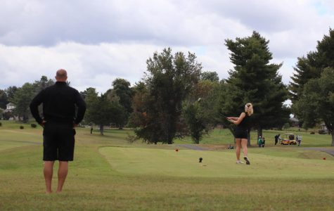 Coach Larry Steinmetz watches as sophomore Macie Brown tees off. Brown's improvement from last season has been large and has served as motivation for her all season.