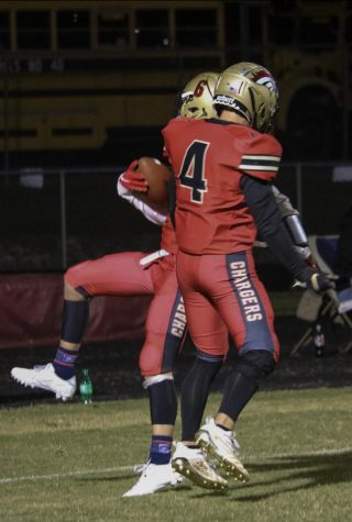 """Senior Receiver Daniel Gilbert jumping and bumping his teammate. Gilbert scored two touchdowns out of the four touchdowns scored by Bullitt East. """"It was a great feeling (scoring two out of the four touchdowns); not just for me, but to see my other brothers, and receivers, scoring and catching footballs, is just as great,"""" said Gilbert."""