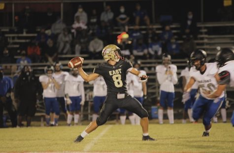 """Senior quarterback Aeron Adams throwing the football, as the other team tries to tackle. Adams was one of the main key players, for this season of football. """"The atmosphere, and playing football, are going to be what I miss most about high school football,"""" said Adams."""