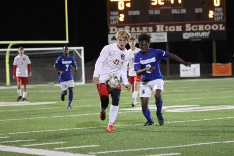 Sophomore Colin Elder fights for the ball against Iroquois High School. He has played both seasons of his high school career on the team and has made an immediate impact on and off the pitch.